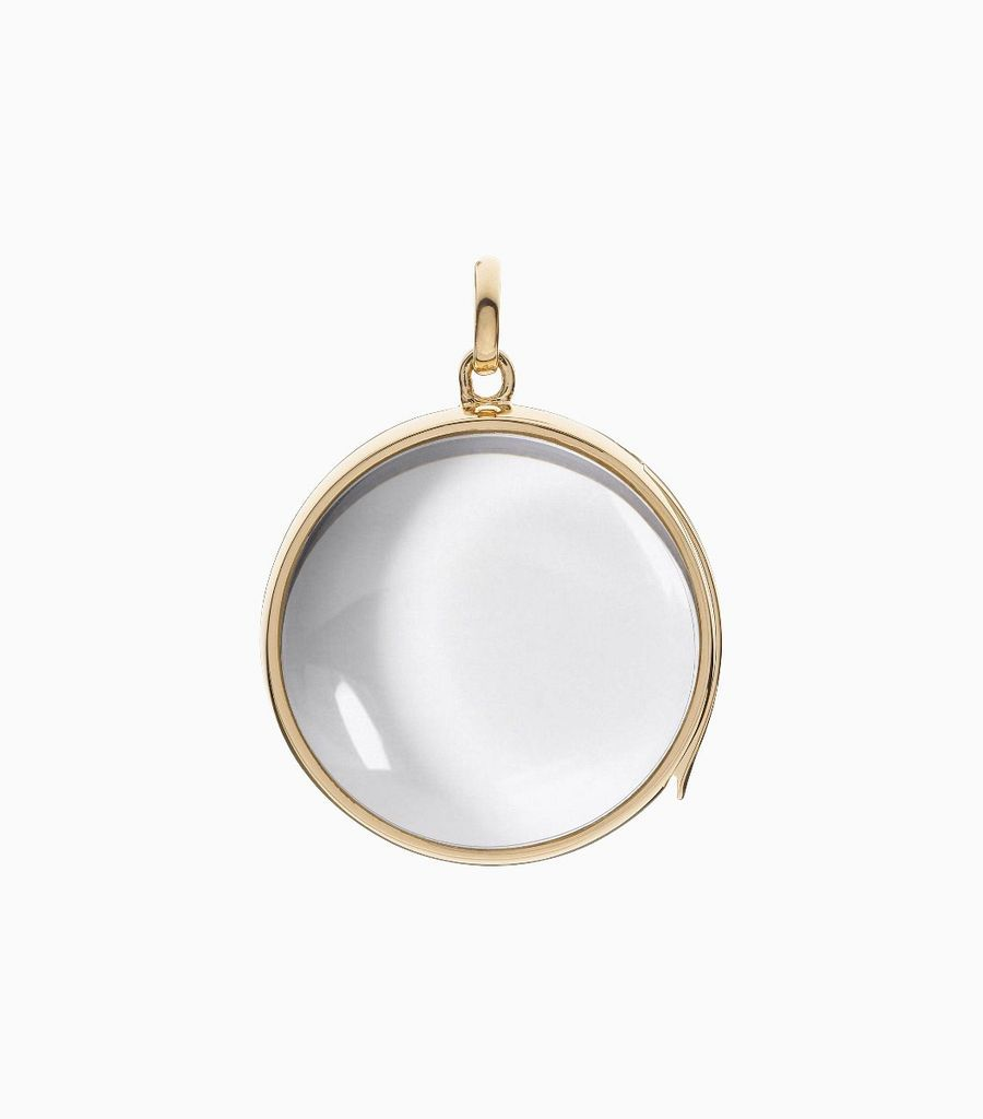 9 carat yellow gold, round locket, set with a bevel edged, crystal glass front and a flat crystal glass back. The locket is designed with a side hindge for secure fastening and measures 24mm